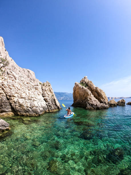 Woman paddling between rocks stock photo
