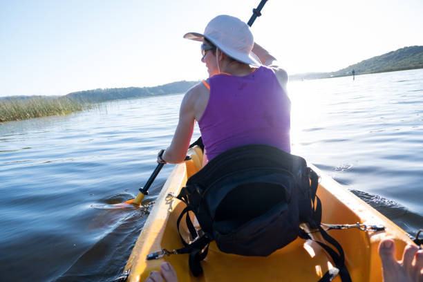 Woman paddling her canoe down the river stock photo