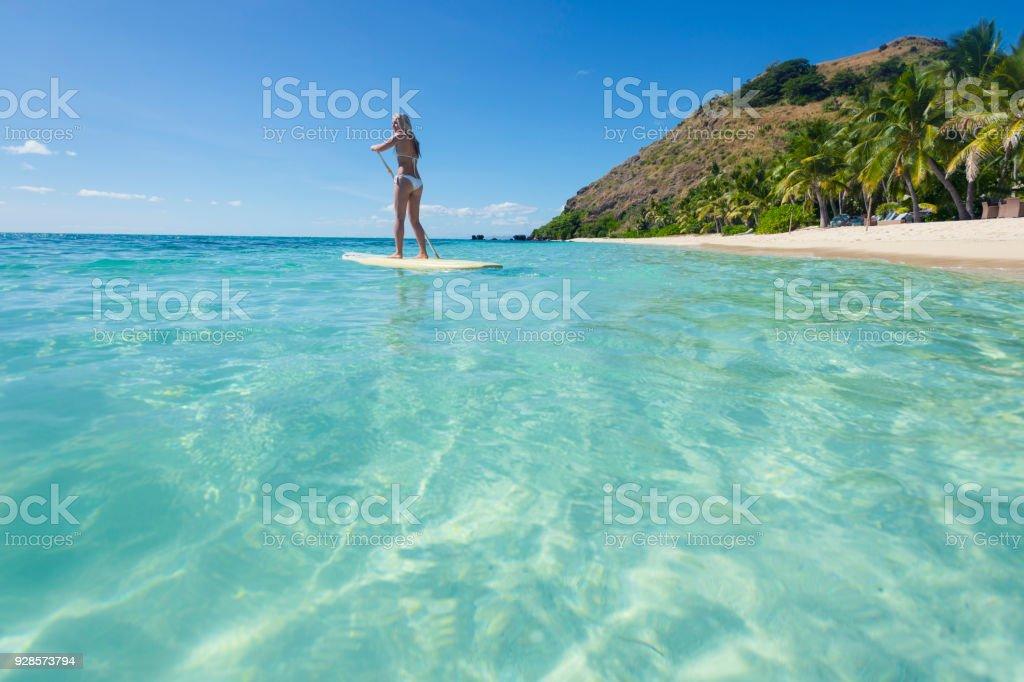 Frau auf einem Stand up Paddleboard paddeln. – Foto