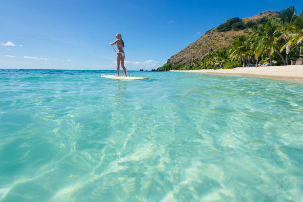 woman paddling on a stand up paddleboard. - fiji stock photos and pictures