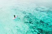 Woman paddling on sup board and enjoying turquoise transparent water and coral reef. Tropical travel, wanderlust and water activity concept. View from back.