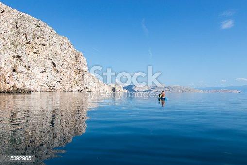 Woman paddling over calm glassy sea