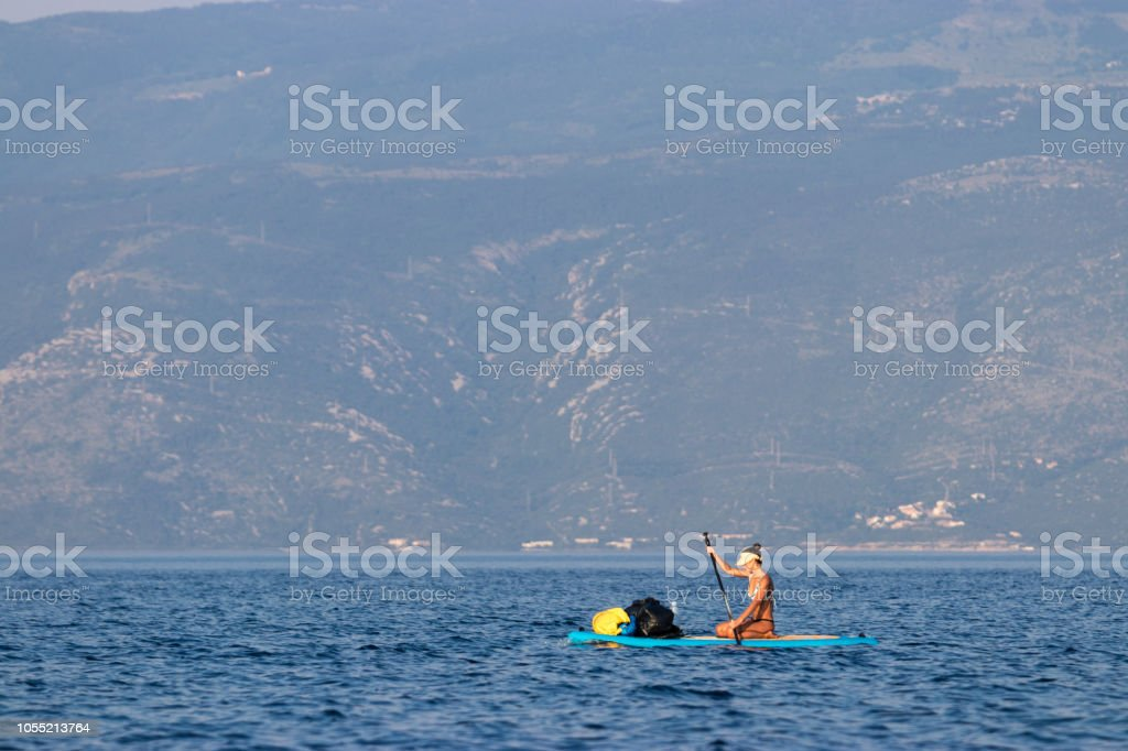 Woman Paddling Over Sea Loaded With Outdoor Gear Stock Photo