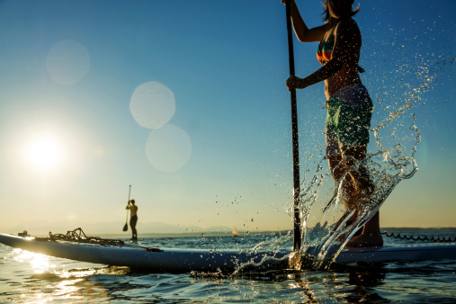 Woman paddling stand up paddle board splashing water.