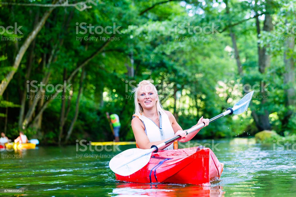 Woman paddling with canoe on forest river stock photo
