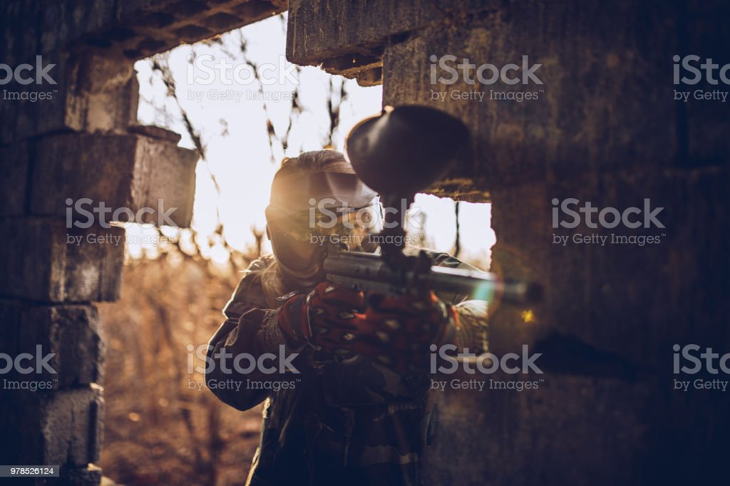 Female paintball player standing with her paintball gun