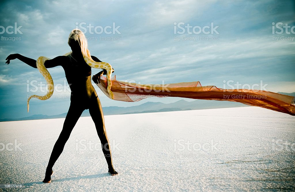 Woman Painted Black and Holding Snake in Desert stock photo