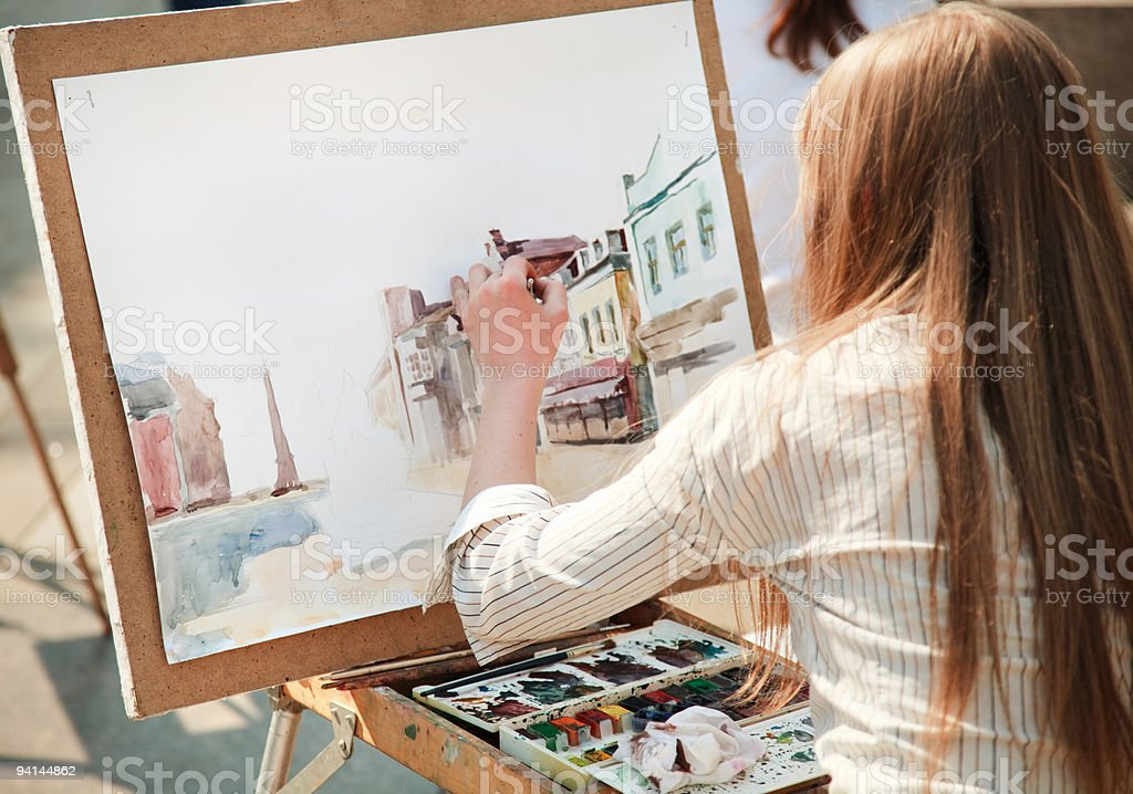 Woman painting a portrait of a city street in watercolors stock photo