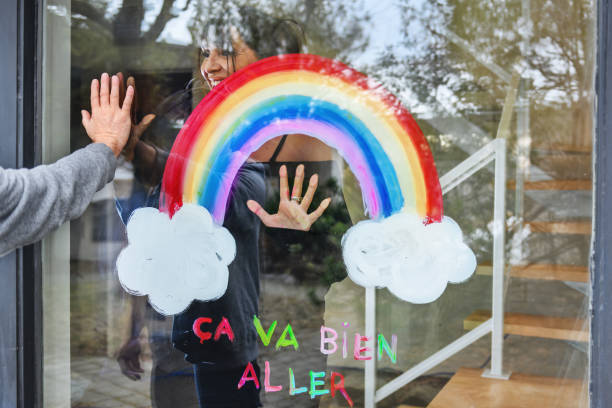 Woman painting a rainbow on a window stock photo
