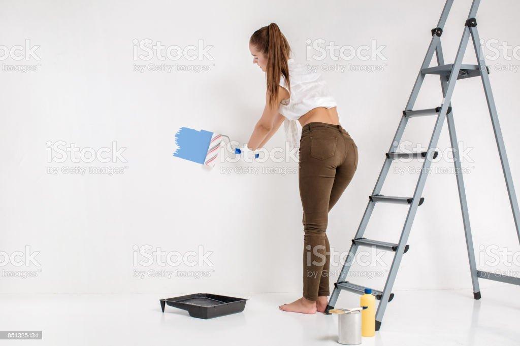 Mujer pintando una pared en casa - foto de stock
