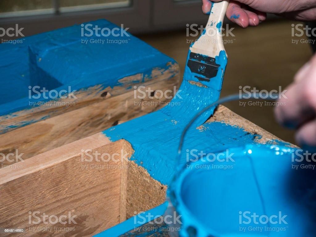 Frau malt eine Holzpalette mit blauer Farbe – Foto