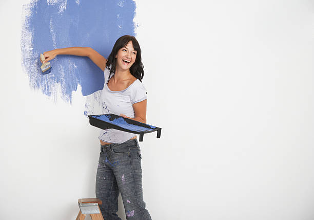 Woman painting and laughing stock photo
