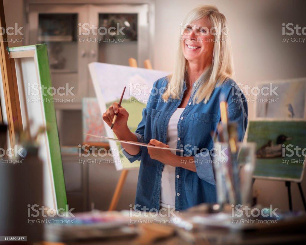 Woman painting art on canvas in artist studio.