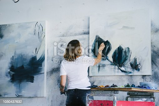 istock Woman painting canvas in art studio 1050437632