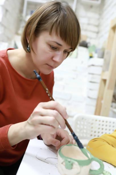 Mujer pintando olla de barro - foto de stock