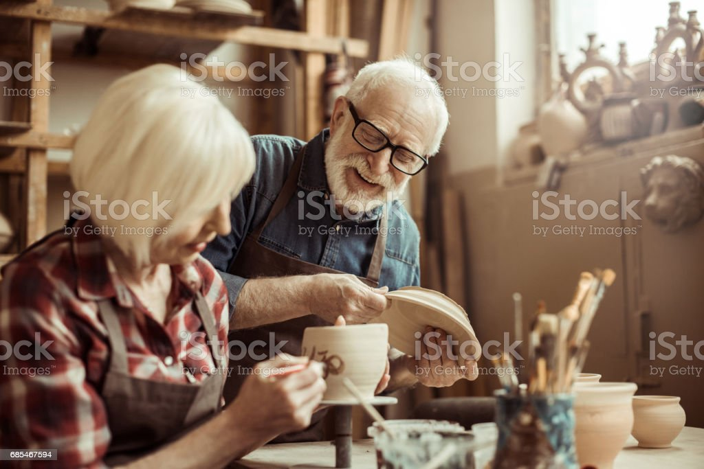 Woman painting clay pot with senior potter at workshop stock photo