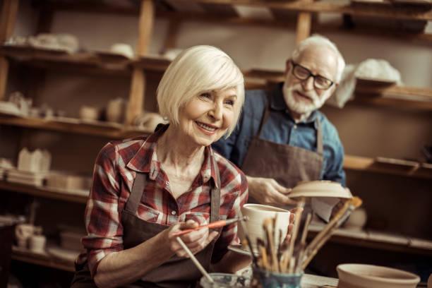 frau malt tontopf mit senior potter am workshop - handbemalte teller stock-fotos und bilder