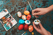 Overhead view on female hand painting easter  eggs on old blue vintage background