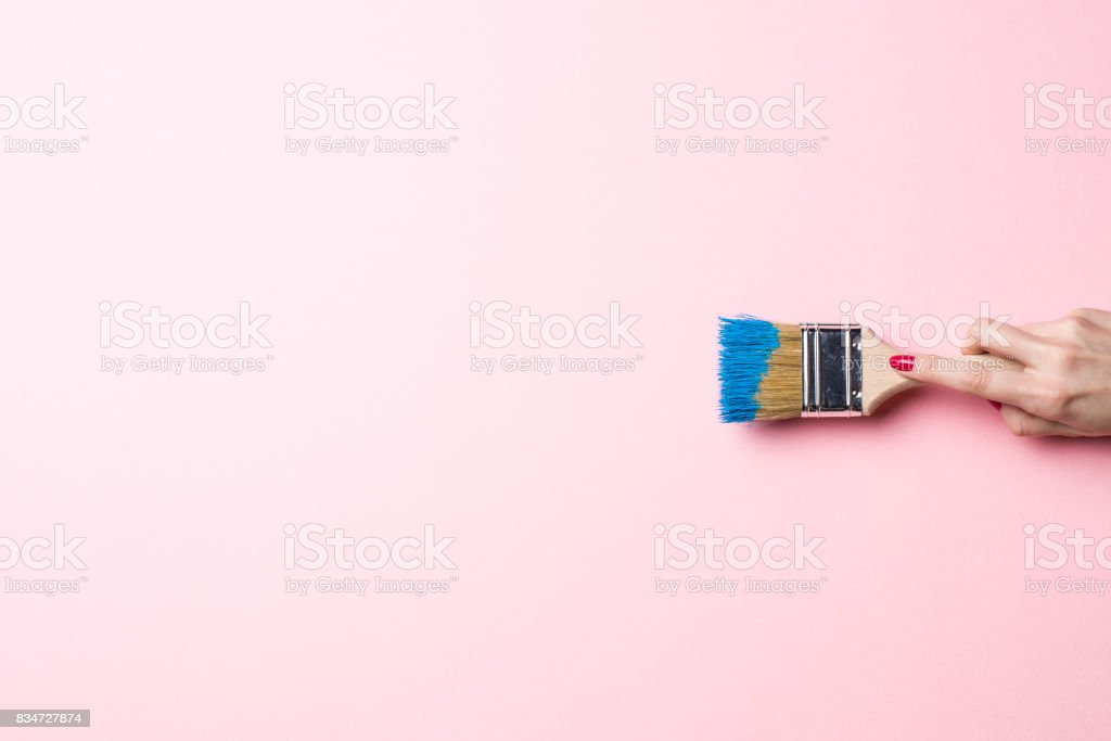 Woman painting empty pink wall stock photo
