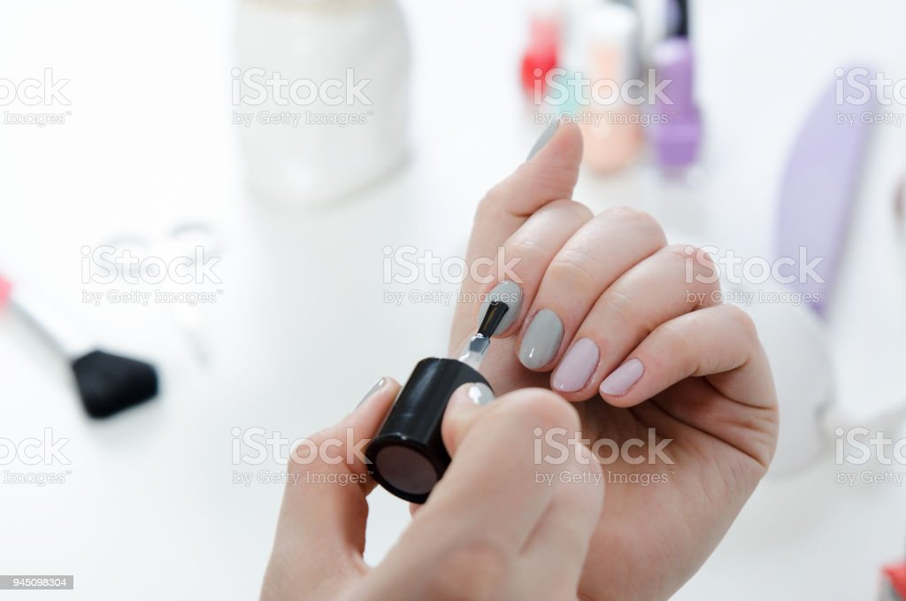 Woman painting her finger nails stock photo
