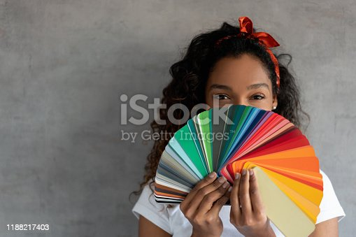 Happy African American woman painting her house and holding a color palette covering her face
