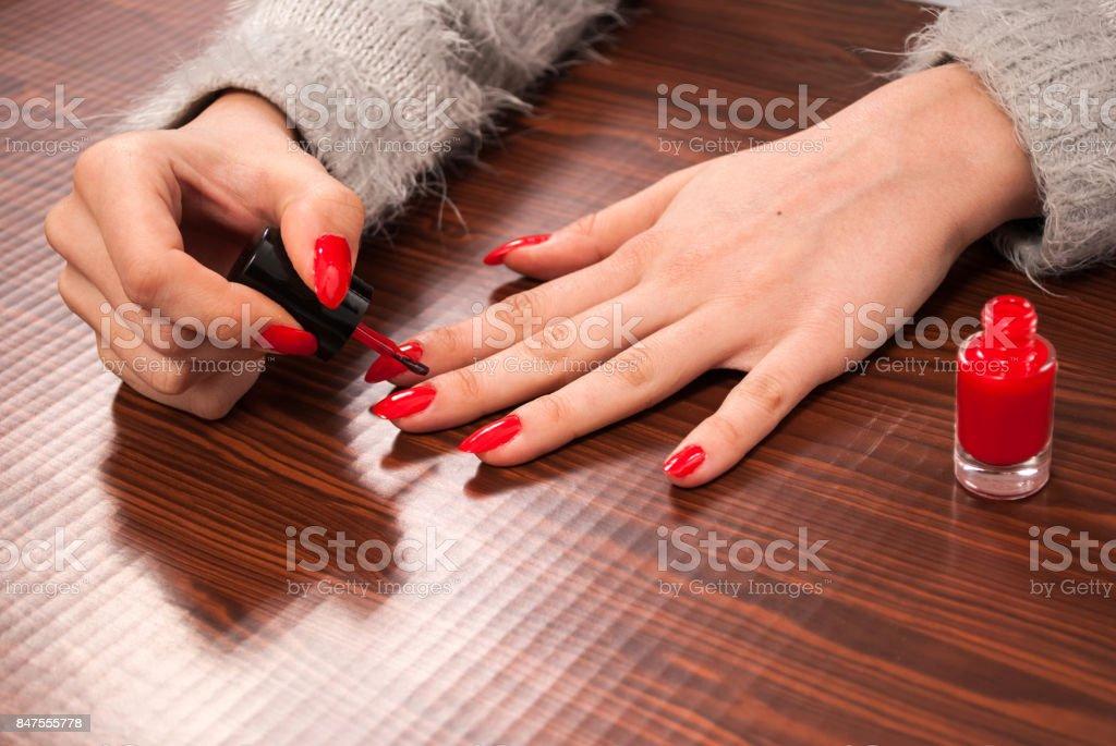 Femme peignant ses ongles sur les doigts en rouge sur le bureau en