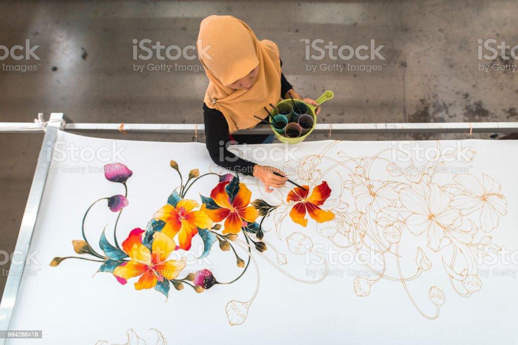 Woman painting in a batik workshop stock photo