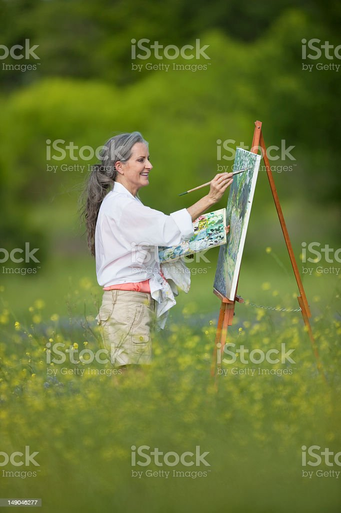 Woman Painting In Field Of Wildflowers royalty-free stock photo