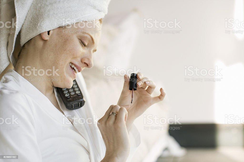 Woman painting nails, talking on phone royalty free stockfoto