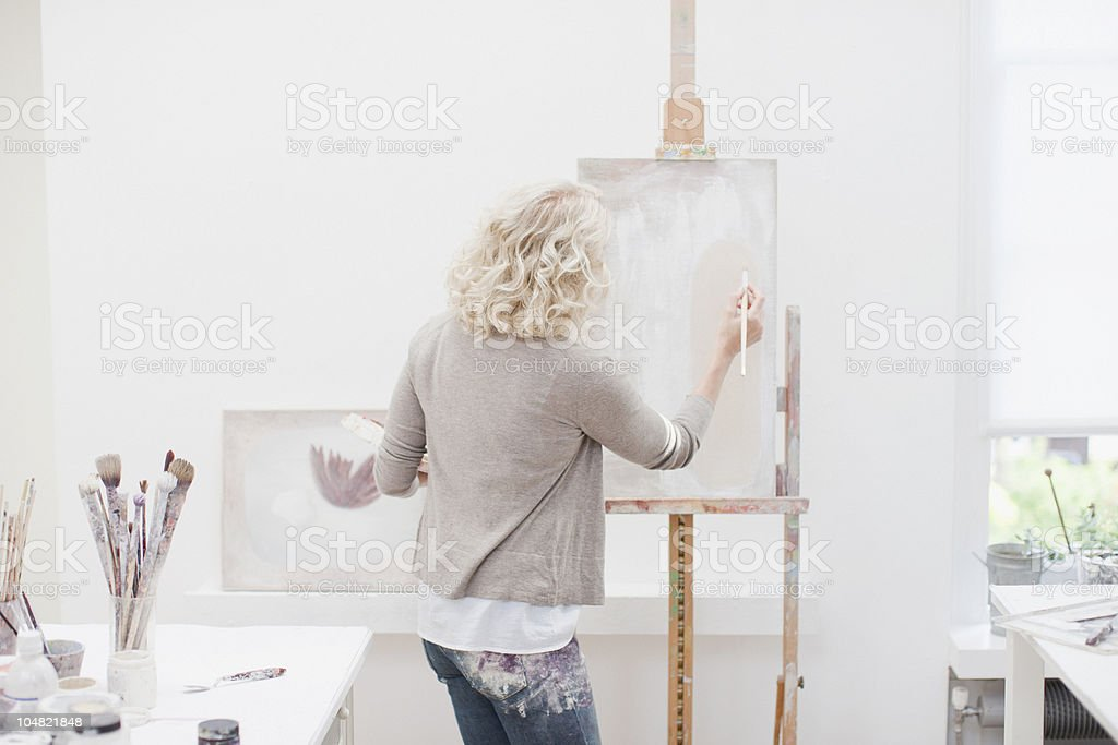 Woman painting on canvas in art studio stock photo