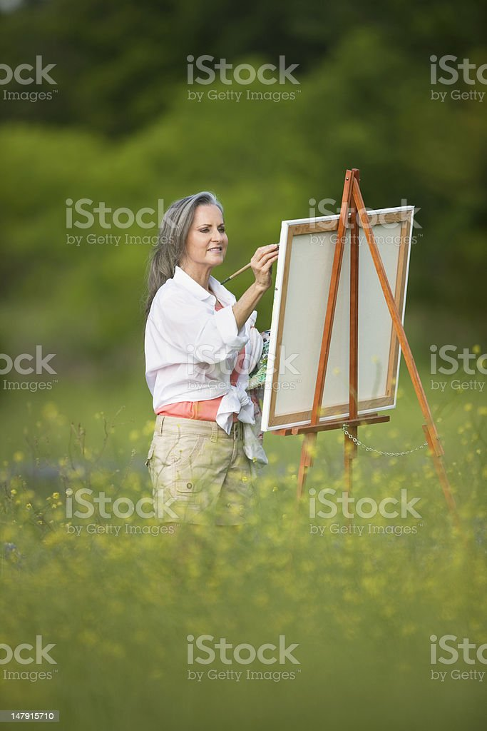 Woman Painting On Easel In Wildflower Field royalty-free stock photo