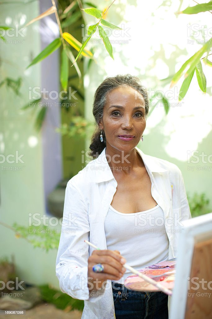 Woman painting on patio stock photo