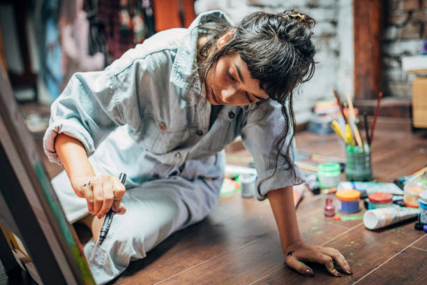 Woman painting on the floor at home One woman, beautiful lady artist, painting on the floor in studio. hobbies stock pictures, royalty-free photos & images