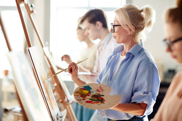 Woman painting Blonde mature woman painting picture on easel with mixed oil colors between her students hobbies stock pictures, royalty-free photos & images