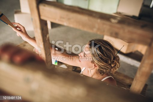 Young beautiful woman painting her walls in art studio