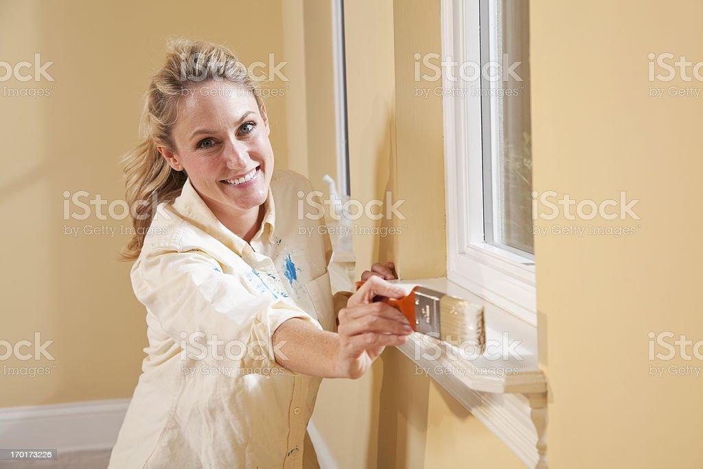 Woman painting window sill stock photo