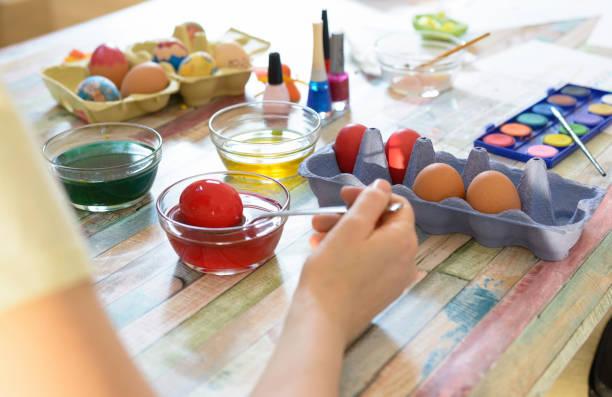 Frau malt bunte Ostereier Familie bereitet sich auf Ostern vor – Foto