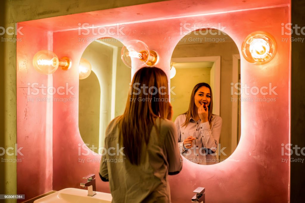 Woman paints lips in the toilet stock photo