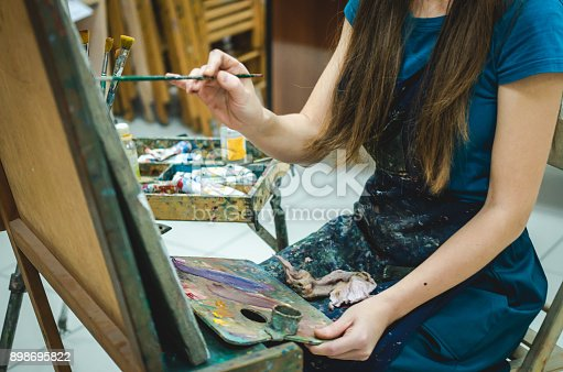 671393252istockphoto Woman paints picture on canvas 898695822