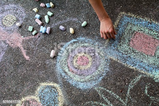 istock Woman paints with colored chalk on asphalt - Stock Image 525561275
