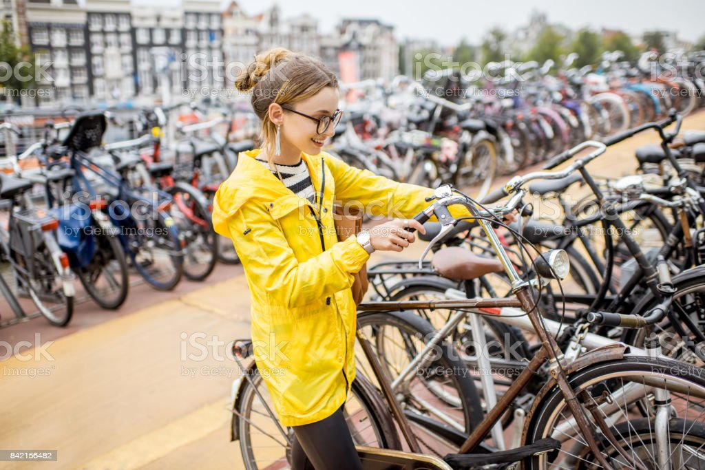 Woman parking a bicycle in Amsterdam stock photo