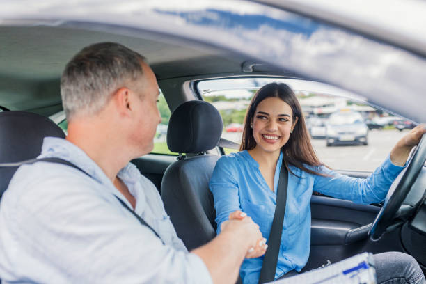 Woman passed Young woman learning how to drive car together with her instructor. Driving school. Happy driving student.  Woman passed. Young woman delighted having just passed her driving test driving instructor stock pictures, royalty-free photos & images