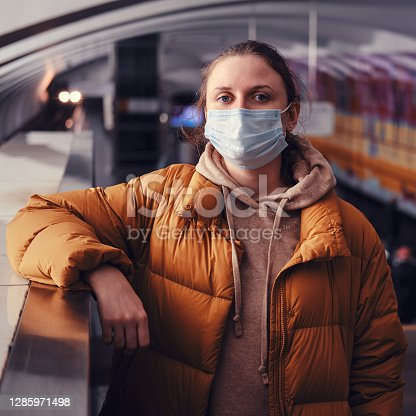 A woman passenger in a properly dressed medical mask stands on a subway platform