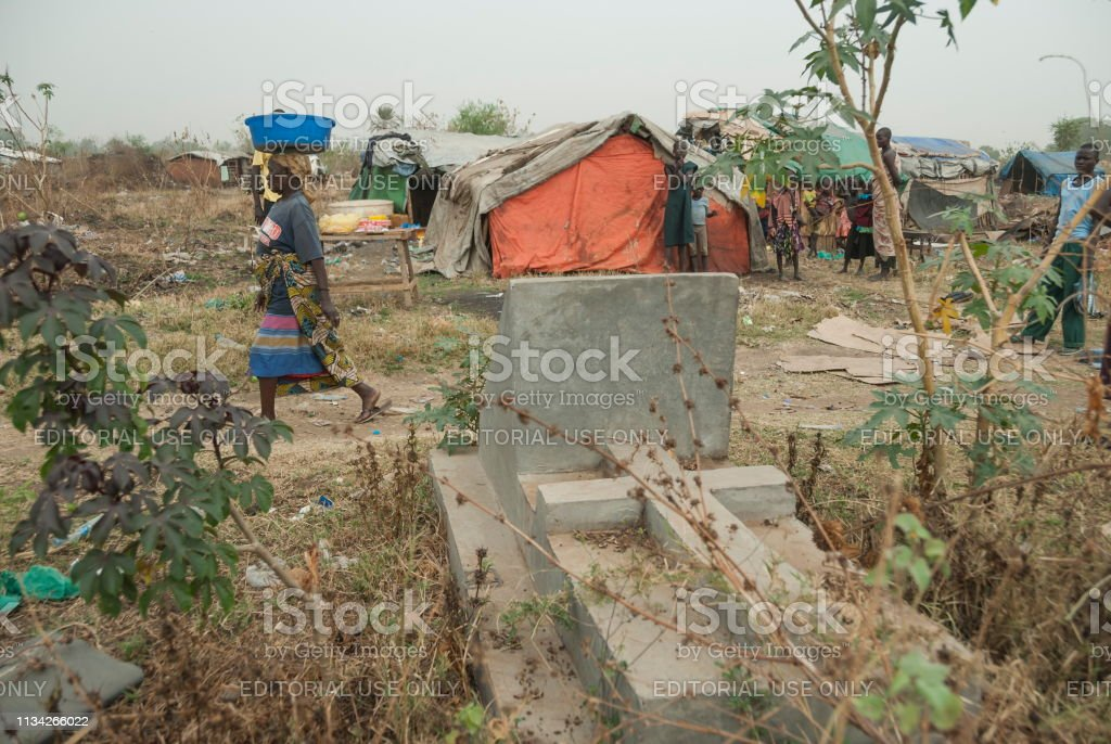 Woman Passes By Stone Grave On Refugee Camp Background Juba