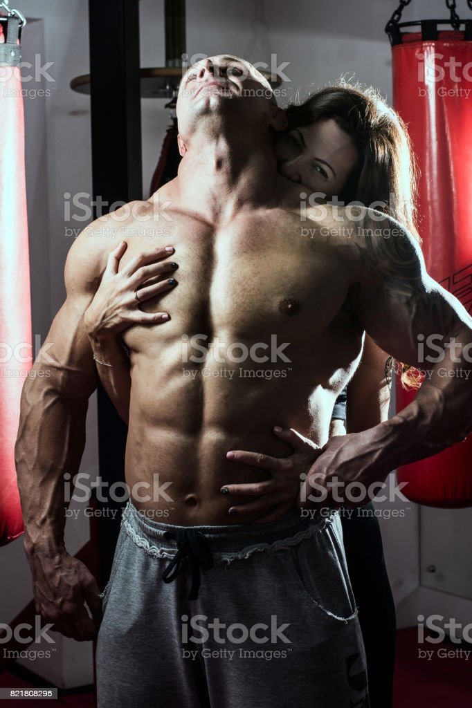 Woman passionately embraces muscular man in the gym stock photo