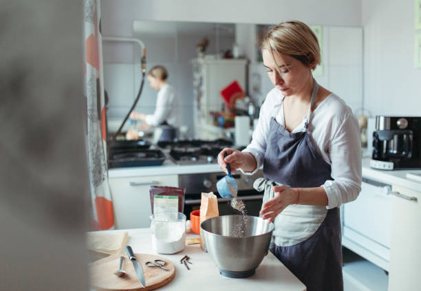 A woman pastry chef or baker  preparing a cake. A woman pastry chef or baker preparing a cake and puts flour in a bowl. making a cake stock pictures, royalty-free photos & images