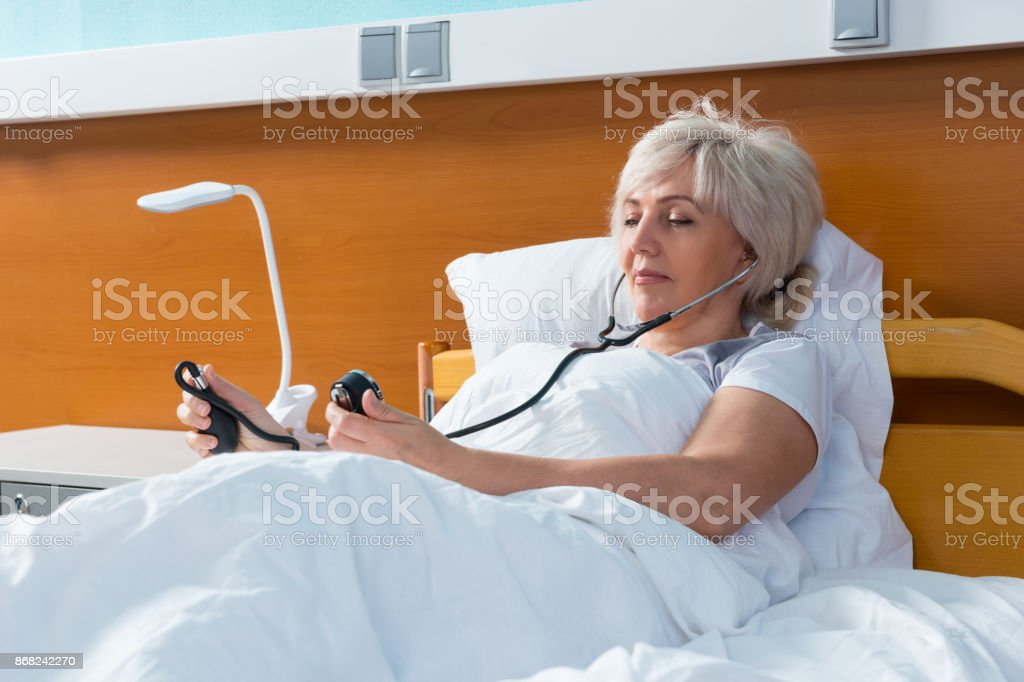Woman patient is measuring the arterial pressure using a medical equipment, while lying in the hospital bed stock photo