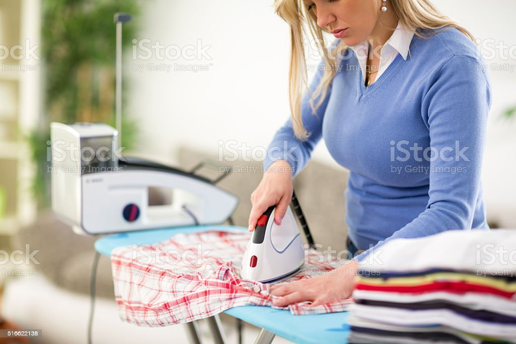 Woman patiently press clothes stock photo