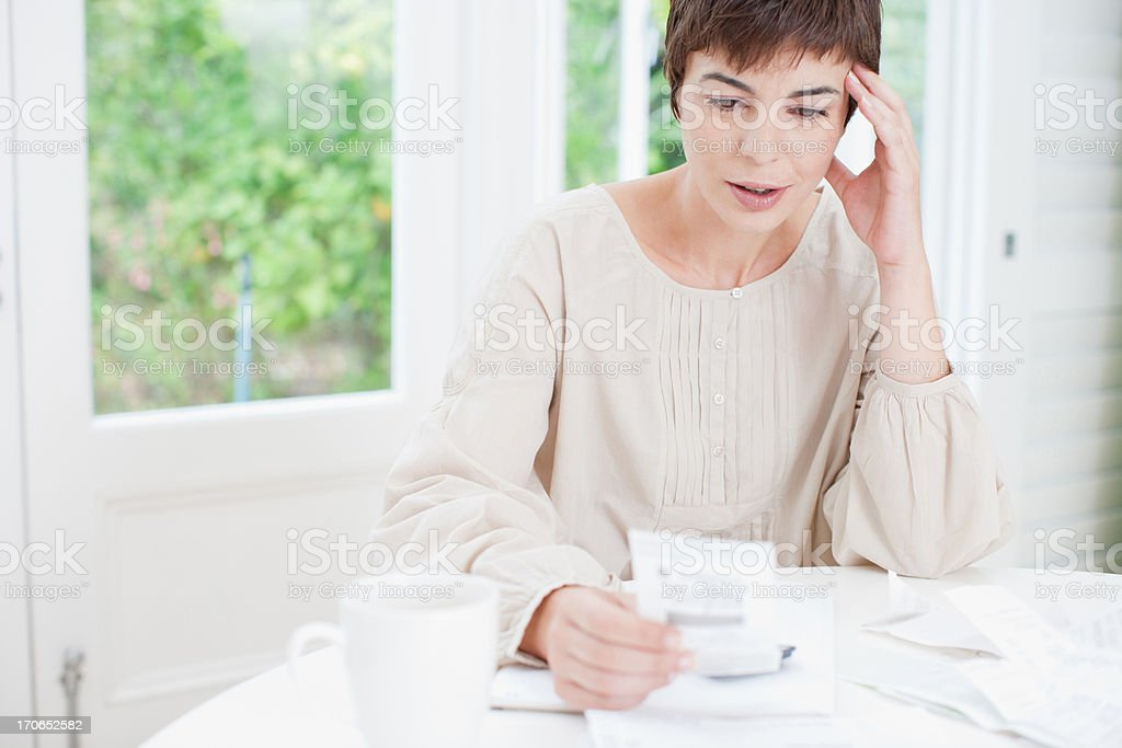 Woman paying bills and looking worried royalty-free stock photo
