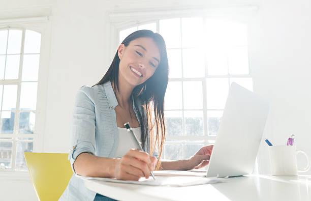 woman paying bills online at home - schreibunterricht stock-fotos und bilder